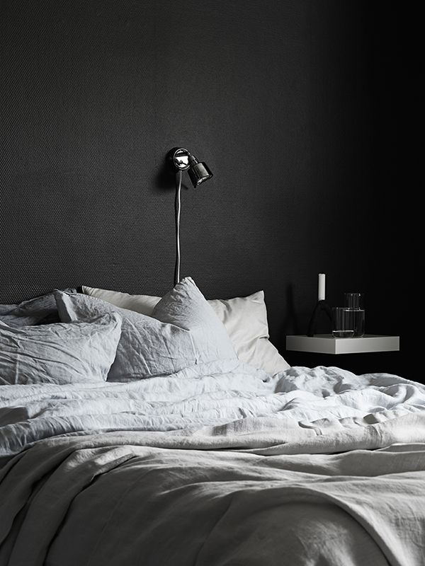 dark walls + textured bedding + floating shelf