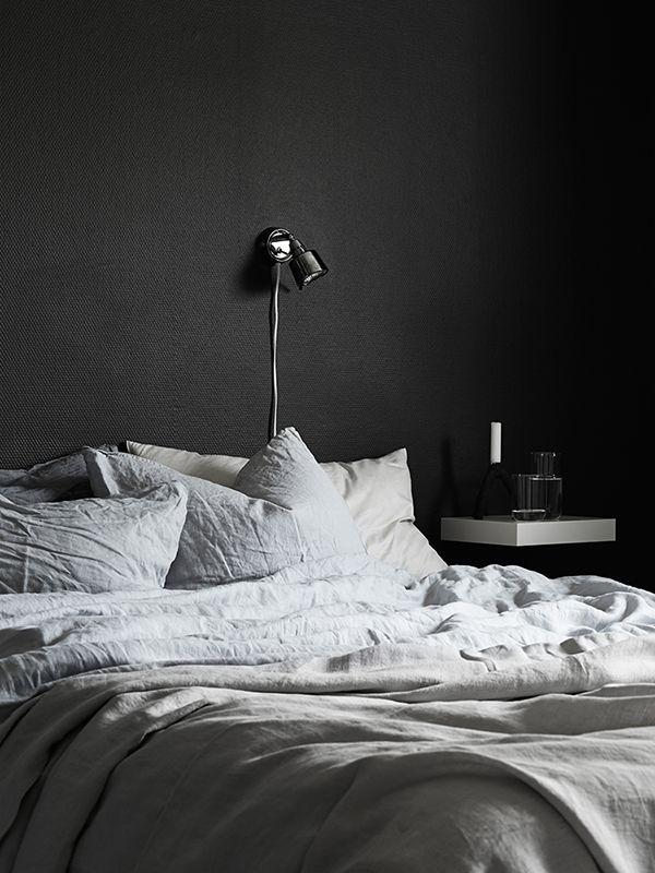 dark walls + textured bedding + floating shelf