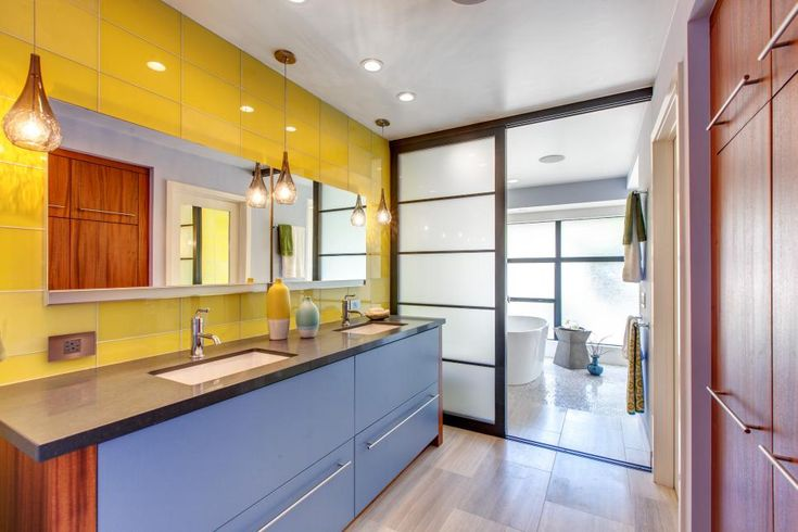 This master bathroom exudes a Zen quality with clean lines in the double vanity, mirror and shoji-style sliding door. Bright yellow tile and glass pendant lights invoke touches of midcentury style while infusing energy into the otherwise serene space.