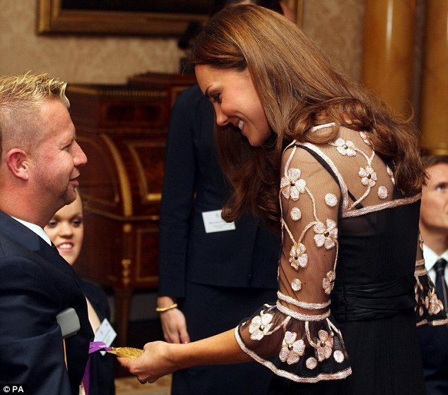 Going for gold: The Duchess of Cambridge inspects Lee Pearson's gold medal for the team dressage