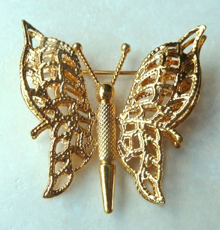 A vintage layered butterfly brooch by Monet.  The butterfly has double layered wings creating a beautiful 3D effect with delicately cut away detailing to the wings all set in gold tone metal. Signed Monet to the back.  Circa 1970's.