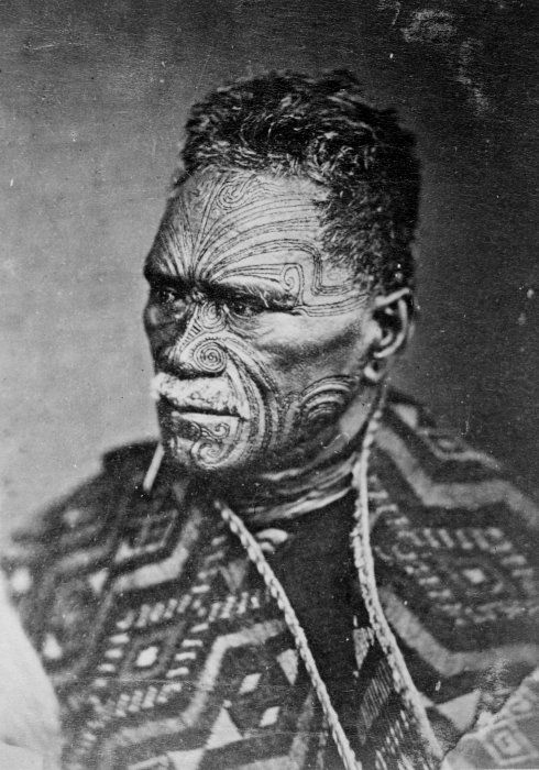 New Zealand | Tawhiao, second Maori King; Head and shoulders portrait of King Tawhaio, with his face in three-quarter profile, looking left. Tawhiao has short dark hair, a moko (facial tattoo), and is wearing a kaitaka (cloak) with the taniko border around his shoulders. | Pulman and Son photography studio 1882