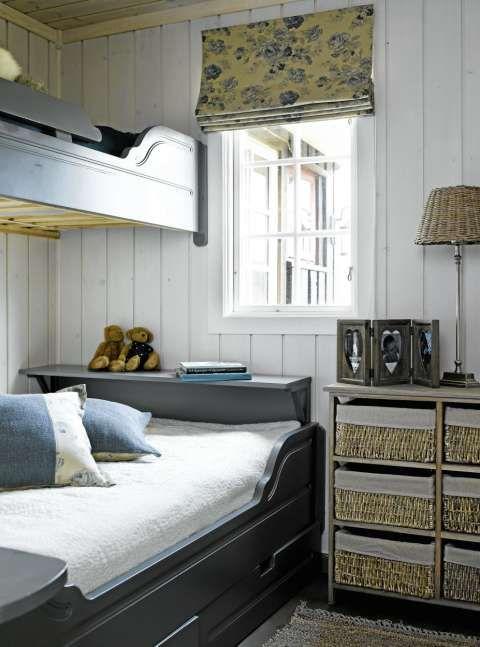 BLÅTT ROM: Dette soverommet er innredet i blåtoner, som passer godt til den gråblå sengen. De gamle furuveggene har blitt overflatebehandlet, og gardinene i lin og bomull harmonerer med resten av rommet. Interiørdesigner Marianne Hemmestad har sydd blå pynteputer i samme stoff som gardinene. Lampen er fra Hemsen Interiør.
