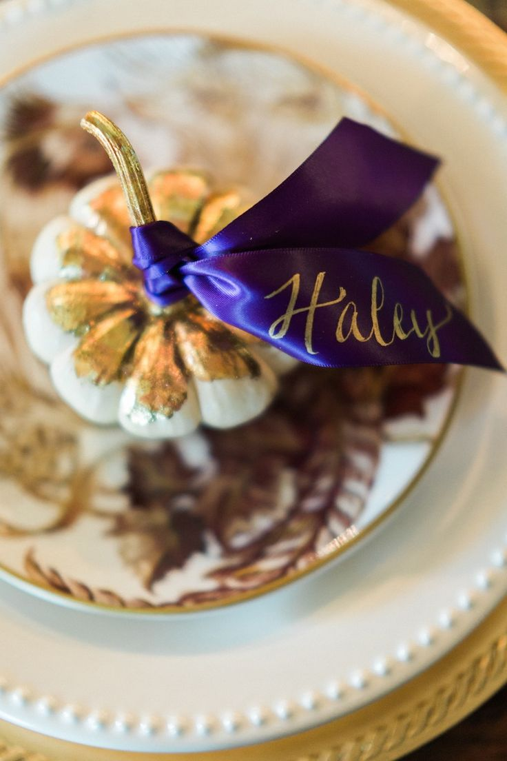Place cards are not only pretty and functional, but they add a personal touch for your guests. Think outside the box — here we used gold leafed mini pumpkins and tied satin ribbon to their stems after adding names to the ribbon with a gold paint pen.