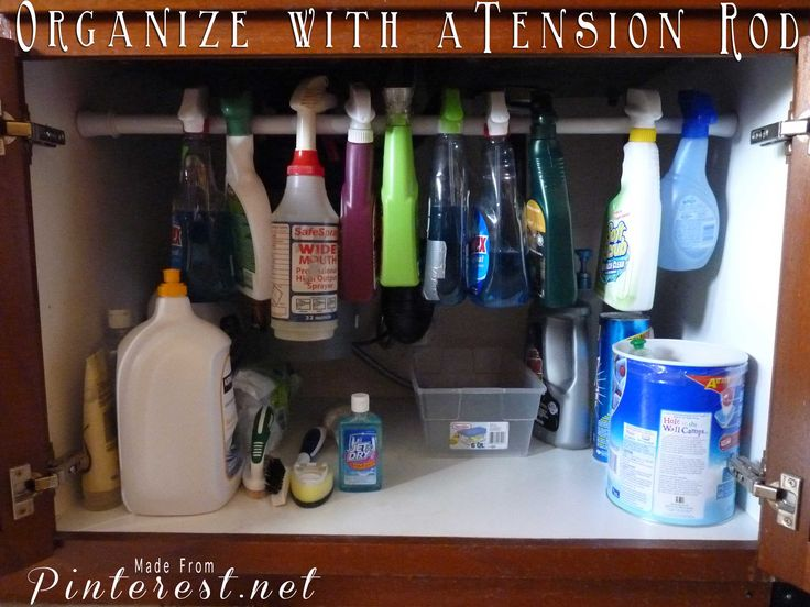 Organize under the kitchen cabinet with a short tension rod.
