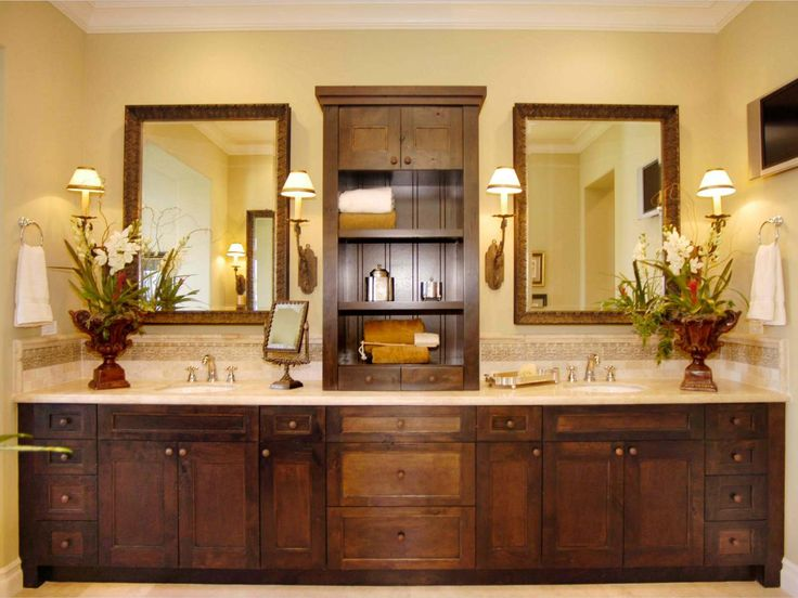 This gorgeous Craftsman-style vanity with dual sinks stretches wall to wall. Dark woods give the vanity an upscale appeal, and a shelf splits the two halves. Wall sconces complement the style of the vanity and provide soft lighting around the mirrors.