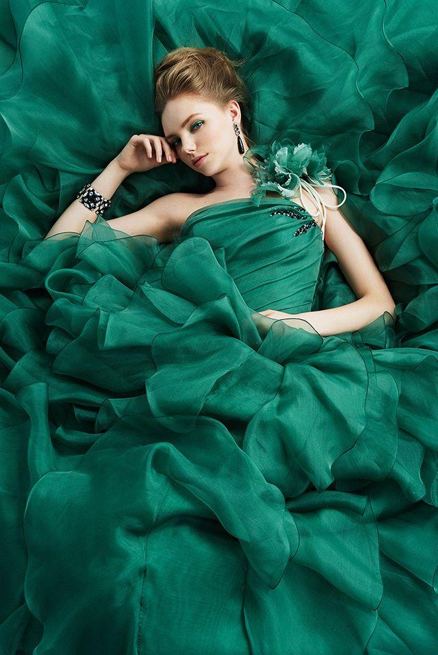 オーガンジーの華やかなラッフルスカートは、ダークグリーンで大人の上品さを演出。ショルダー部分にあるコサージュで顔まわりに彩りを添えて。