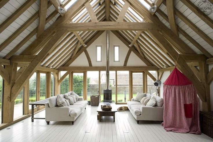Simple and elegant barn room extension with sling-brace oak frames and freestanding woodburner