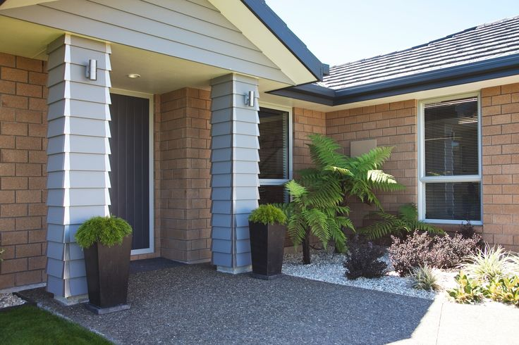 Home entrance detailing; Light blue weatherboard with stainless trim in front of a classic light brick.