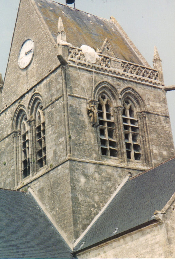 The church at Sainte-Mère-Église, Normandy, France.  The night before the D-Day landings US Paratroopers landed in the center of this town, which was a German headquarters, while the whole town was out fighting fires.  They were slaughtered.  One ended up hanging by his chute from this church tower, and survived.