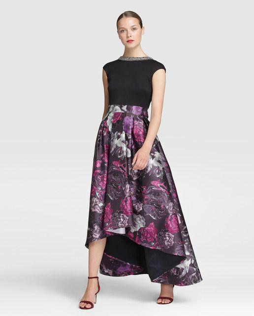 Vestido largo de fiesta con efecto dos piezas. Cuerpo en color negro, de manga corta y escote redondo con pedrería. Falda con jacquard floral en tonos rosas con lazada en la cintura.