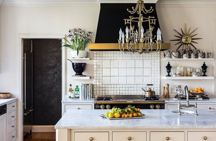 Fashion designer Kim Bachmann's home may be a Beaux Arts building that dates back to the 1920s, but her kitchen is brimming with modern-day style. The open shelves flanking the bold black hood feature accents that cement the space's white, black, and gold color scheme.