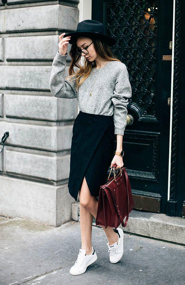 Street style look com saia social fenda, suéter cinza, tênis branco e óculos…