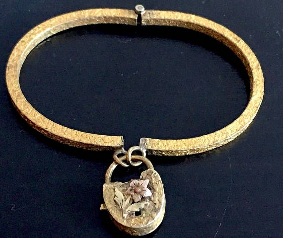 This antique padlock clasp bangle bracelet dates from the last half of the 19th century, circa 1875 (ish) and features a tiny ornate and textured yellow and rose gold heart. There is a rasied applique flower on the heart. I believe the metal is Pinchbeck but there are no markings and this is just my best guess based on the few Pinchbeck items Ive seen over the years. The lock functions as a clasp and closes securely. It is opened with a push button on the side. Pinchbeck is a form of brass…