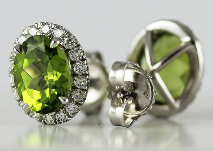 A pair of white gold diamond and emerald earrings.