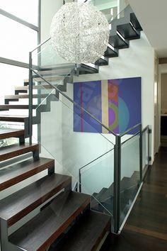 Photo DT45 - ESCADROIT® 2/4 Tournants avec Paliers Intermédiaires Carrés. Escalier dintérieur design en métal, bois et verre pour un intérieur contemporain type loft. Marches en tôle pliée habillée par plateau bois y compris nez. Option limons découpés en crémaillères en L. Rampe et garde-corps composés dune main courante et de montants en fer plat graphique et de panneaux verre feuilleté clair pour la transparence, fixation parclose du verre aux montants. Rampes et garde-corps en protectio