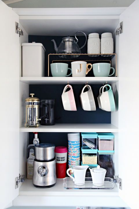 Add hooks to the bottom of a cabinet shelf to make it easier to grab cups in the morning. Click through for more on how to organize coffee cups.