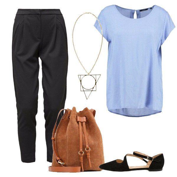 L'outfit di sapore semplice è composto da un paio di pantaloni neri con lunghezza alla caviglia ed una camicetta con scollo tondo ampio. Il look si completa con la borsa a tracolla in pelle color cognac, la ballerina nera con cinturino alla caviglia e la collana in metallo con raffinato pendente.