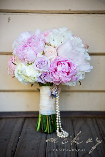 Pink and white wedding bouquet with a pearl string