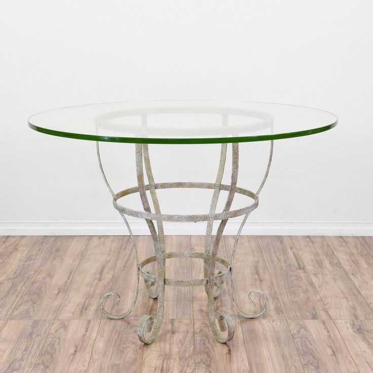 This outdoor table is featured in a durable wrought iron with a distressed white paint finish. This patio table is in great condition with curved swirl legs, a pedestal base and round glass table top. Perfect dining table for a patio or porch! #mediterranean #tables #diningtable #sandiegovintage #vintagefurniture