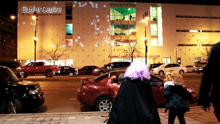 """Buhler Centre Interactive Building Projection. As passers-by waved their hands, they saw outlines of themselves interacting with the balls and were able to """"throw"""" them around like billiard balls. The virtual balls not only interacted with the people but also with the physical building, flowing around the windows and bouncing off the iconic 'fins' for which the Buhler Centre is known."""