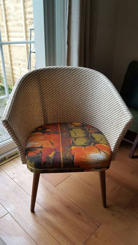 Retro bedroom chair similar style to Lloyd Loom with wooden legs possibly teak comfortable vintage wicker chair funky orange pattern fabric in nice clean condition. Probably dates to the 1960s / 1970s, with a cute gold coloured metal trim around the front edge visible in the photos. The legs will be removed for postage as they do screw off. If you have any questions please ask, I am always happy to help. For international postage price please provide a city and postcode and I will get back…