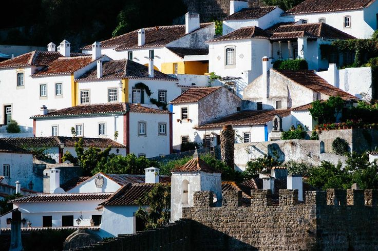 Óbidos is a medieval fortified town in central Portugal, dramatically perched upon a sloped hilltop, bursting with rural charm and cobblestone streets.