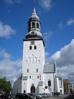 Catedral de San Botulfo de Aalborg. Dinamarca. Es una iglesia-salón gótica de finales del siglo XIV construida de ladrillos. Su planta incluye tres naves, un coro, una torre occidental, un vestíbulo adyacente a ésta y una sacristía en el costado norte. La torre presenta cuatro relojes idénticos en cada uno de sus lados, obra del joyero de Hamburgo Frederich Vilhelm Meyer. En cada esquina, los relojes tienen esculpido un gallo.