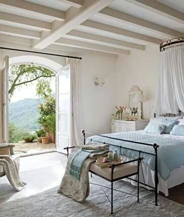 Beamed ceilings, beautiful view, open and airy... Love this soft colour pallette with black iron bed.