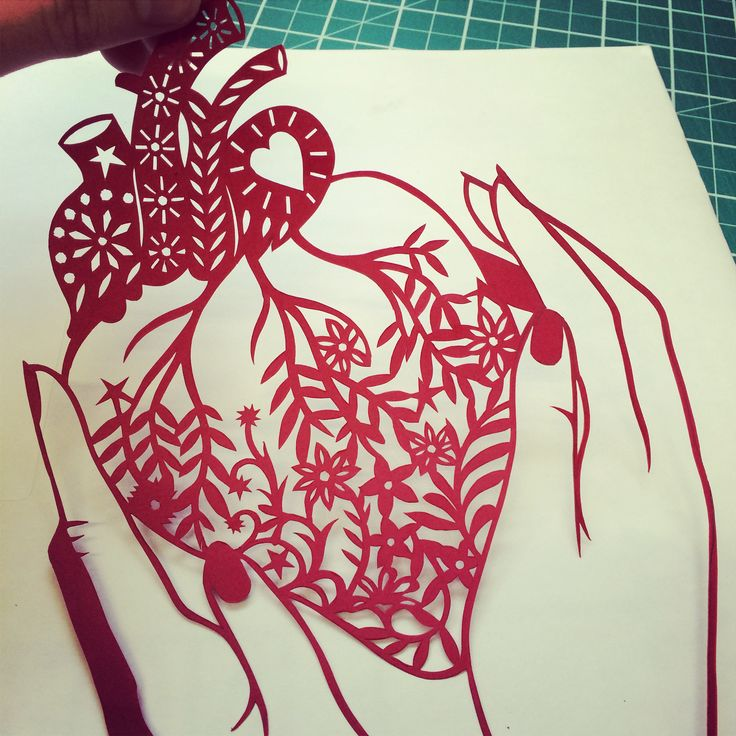 Hands holding an anatomical heart with flowers. Handmade papercut by Poppy Chancellor