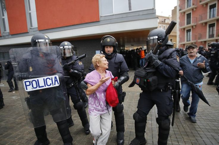 La policía disuade a una mujer de acercarse al lugar de votación en la escola Mediterránea de la Barceloneta (Barcelona).