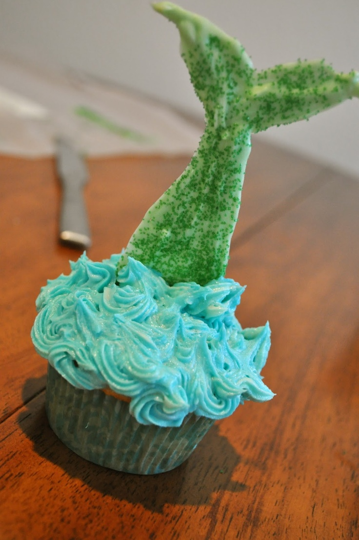 Mermaid Cupcake. The tail was made with Wilten Candy Melts, but I bet you could also just melt some white chocolate chips, mix in a little green food coloring, draw the tail shape, add some sprinkles, and let it cool and harden.(im gonna try to make tail from fried tortilla shell with green sprinkles..just a lil fyi..)