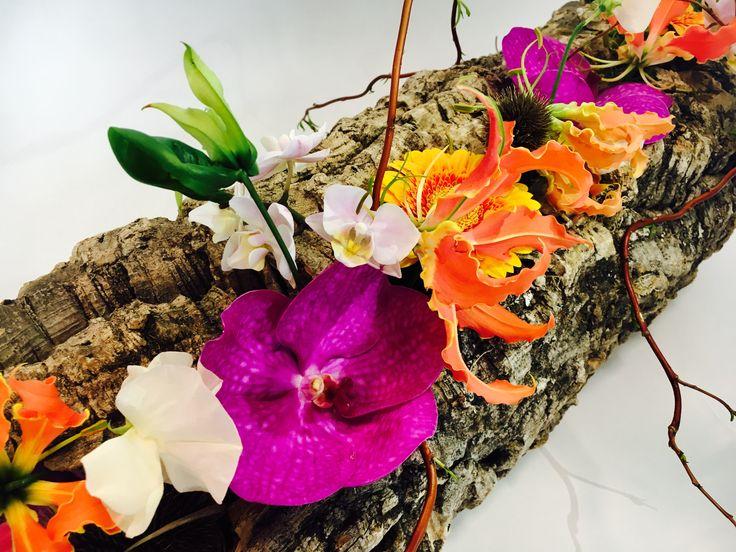 - Stijl van het rouwbloemwerk: is modern. - Materiaal keuzen: boomschors, Anthurium flamingo, gedroogde distels, Gloriosa rothschildiana, Gerbera spanish, Orchidee vanda, Lathyrus odoratus, Phalaenopsis cultivars, Paastakken en Dille zaaddoos. - Verzorgingsadvies: water geven op de schotel, zo koel mogelijk weg zetten. Niet in de zon, recht neerleggen. - Verkoopprijs: €100,-. Evaluatie: Ik heb bij dit bloemstuk veel geleerd hoe je steekschuim heb beste kunt bevestigen.