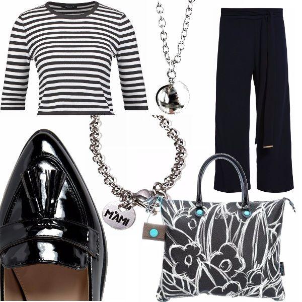 Un outfit semplice e raffinato nel suo genere, mocassini classici di pelle lucida, pantaloni a tre quarti, maglia a zebrata, accessori lucenti e la particolare borda a fiori bianchi su fondo nero della Gabs.