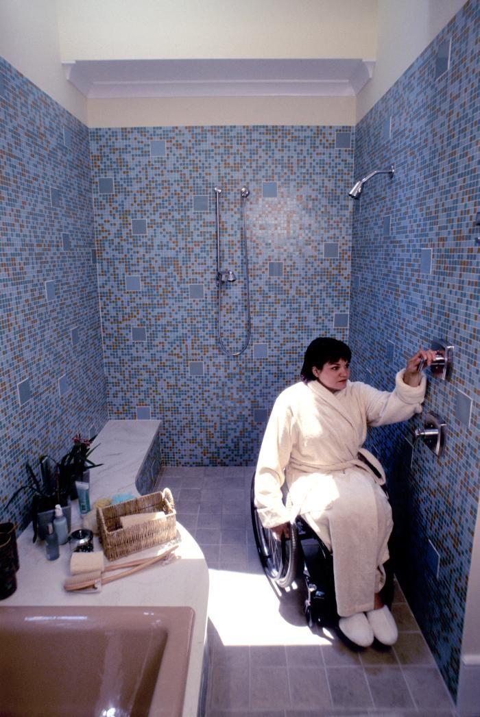 Femme en fauteuil roulant profitant des aménagements de sa salle de bains (Droits; Center for Universal Design, Public Domain)