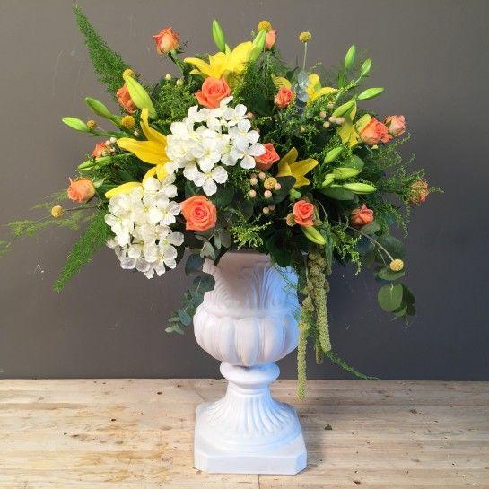 Σύνθεση σε Vintage κεραμικό λευκό κασπώ με κίτρινα λίλιουμ, πορτοκαλί τριαντάφυλλα, ορτανσία, υπέρικουμ, κρασπέντια, σολιντάγκο και διάφορες ιδιαίτερες πρασινάδες.Διαστάσεις κασπώ; 38*38*53