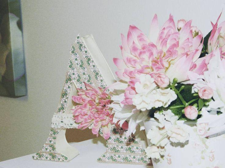 Letra cartón y cartulina decorada. Y maceta con flores artificales a juego