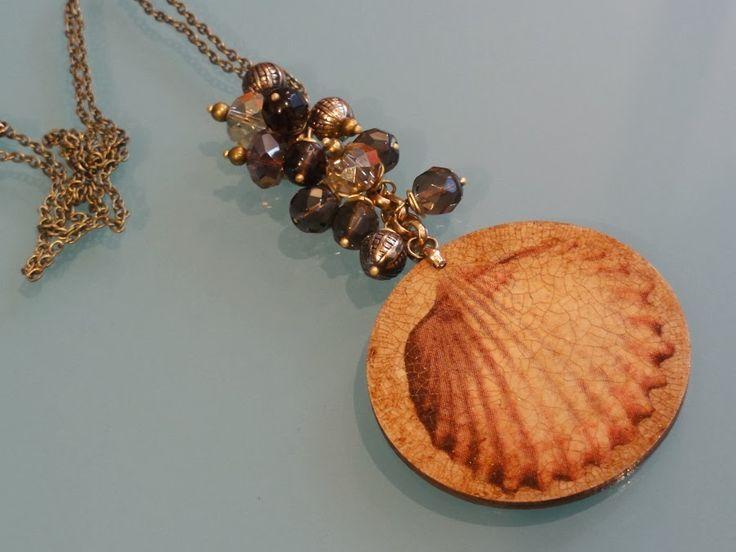 Morski - Nowość!  Niepowtarzalny wisior wykonany techniką decoupage, z efektem przestrzenności oraz pastarzanych i złoconych spękań. Każda ze stron wisiora jest ozdobiona inną muszlą. Długi łańcuszek w kolorze starego złota oplatają fasetowane kwarce dymne oraz kryształy Swarovskiego briolette i metalowe ozdobne zawieszki. Długość drewnianej zawieszki - 5cm, długość całej zawieszki z kryształami - 10cm