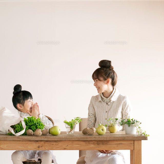 野菜が転がったテーブルに座りふざける親子 (c)hororo style