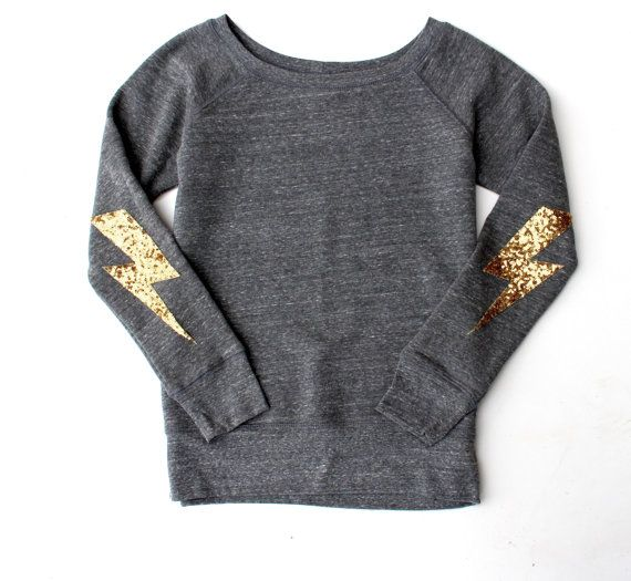 This darling sweatshirt is sure to dazzle your friends.  Handmade lightning bolt patch made with quality sequin fabric not an iron on transfer. Patch is sewn on to the shirt.  Heather Grey - Photo 1 Acid Grey - Photo 2 Black - Photo 3 White - Photo 4   Note: Elbow patches are not sewn on to the shirt in photos, but will be when shipped.   Sweatshirts are womens sizing and fit true to size. They are not oversized unisex sizes. 50% Polyester, 37.5% Combed and Ring-Spun Cotton 12.5% Rayon…