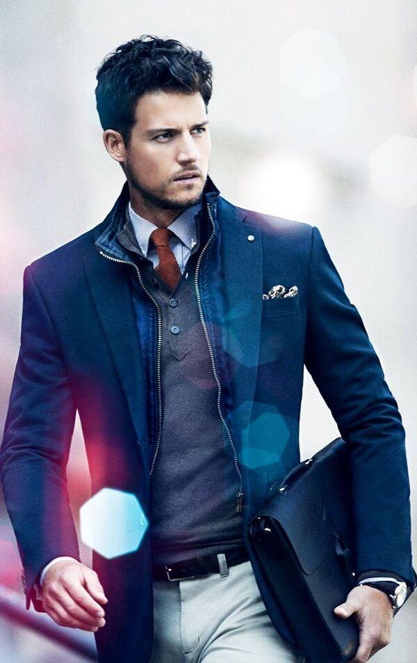 Nette #zakelijke #outfit met donkerblauw #colbert en grijze #pullover op een lichte broek. Net #overhemd met #stropdas en #aktetas maken de zakelijke stijl af. #suit #tie #blue #briefcase