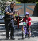 Chief Mark O'Connor helps Riley Martin through an obstacle course during a bike rodeo Thursday, May 30, 2013, at the Hillsborough Police Department. About 30 kids came out to learn the rules of the road for bicyclists. (John Green/Bay Area News Group)