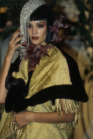 * John Galliano for Dior Spring/Summer 1997 Model wearing a yellow brocade fringed wrap coat with black fur trim, beaded silver hat, and maroon fabric flower choker ca. 1997 © Guy Marineau