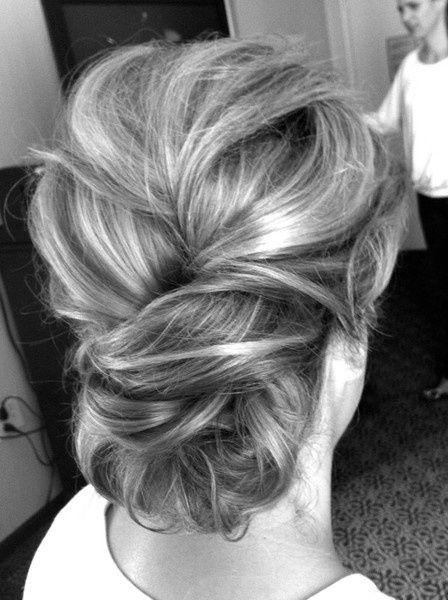 Les longs cheveux de cette femme ont été ramenés vers l'arrière pour former un gros chignon. On remarque que le coiffeur a commencé par faire une très courte tresse avant de réaliser le chignon. Il a laissé une certaine souplesse à la chevelure sur le dessus de la tête.