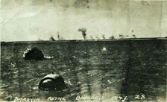 Darwin in the distant skyline being bombed, two sea mines float in the foreground.1942