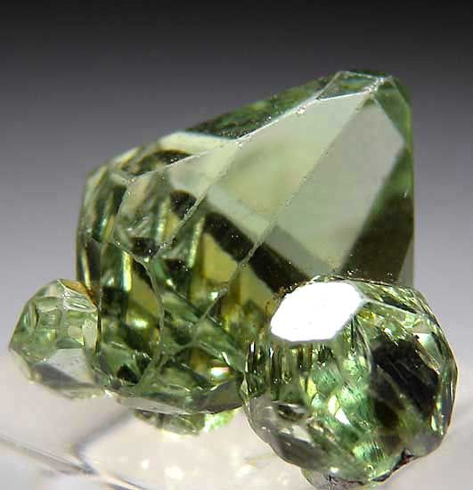 TSV33 - Tsavorite $ 900 SOLD Merelani Hills, Lelatema Mtns., Arusha Region, Tanzania small cabinet - 1 x 1 x 1 cm Cluster of 3 gem Tsavorite crystals, best of the lot. Main crystal is 1cm. Well crystallized all around and glassy and undamaged. Very rare to find Tsavorites in clusters and in such gemmy, complete crystals. These formed on the edges of Graphite crystals, so bottom has a few indentations from the thin Graphite blades, however even the bottom has crystallized faces.