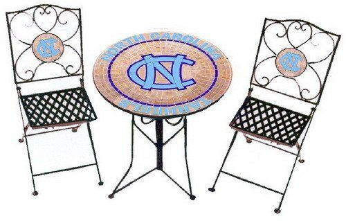 """North Carolina Tarheels Bistro Table and 2 Chairs by Traditions. $279.99. Table: Genuine Leaded Stained Glass Mosaic top on mortar base - wrought iron. Chairs: Stained Glass mosiac school logo in wrought iron chair backs. Dimensions: Table 27"""" dia. X 30"""" tall.. Officially Licensed Product. North Carolina Tarheels Bistro Table and 2 Chairs - Show Your Team Colors with this Officially Licensed high quality product by Traditions ArtGlass Studios. Beautifully handcrafted..."""