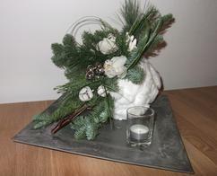 een tempex bal bekleed met wattenbollen en een uitsparing erin gemaakt hierin een stuk oase gezet en opgevuld met kerstgroen en orchideen