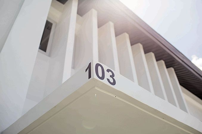 """Although the couple knew that they wanted a minimalist home, every house in their village had to have a Modern Asian facade. To meet this requirement, they opted for exteriors with a row of narrow white beams. Since they were told that it was bad luck to have a house number that adds up to four, a number that means death, Calvin and Marga decided to separate the numbers on the awning. The number """"1"""" is placed on the other side.�"""