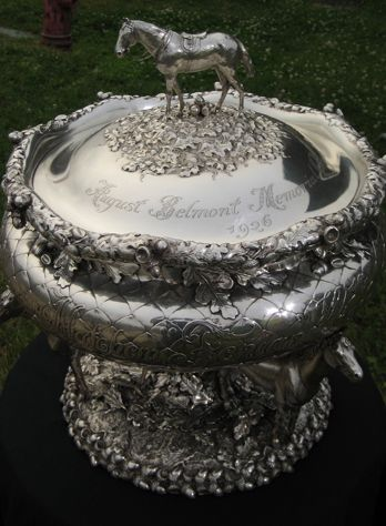 Belmont Stakes Trophy. The August Belmont Memorial Trophy is presented each year to the Belmont Stakes winner.  The horse represented in silver on top is Fenian, the 1869 winner. The three horses supporting the bowl are Herod, Eclipse, and Matchem.